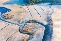 Freezing morning in countryside. Foggy rural area near river aerial stock photography