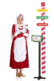 Freezing at the North Pole. Mrs. Claus shivering by a Christmas-decorated mail box and a North Pole sign.   on white Royalty Free Stock Image
