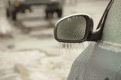 Freezing rain ice coated car. Black vehicle car covered in freezing rain, Icicles hanging from side mirror. bad driving weather in freezing rain Royalty Free Stock Image