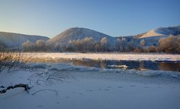 Freezing river from the hilly banks and large ice floes. A sunny day with a cloudless sky Stock Photos