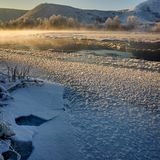 Freezing river from the hilly banks and large ice floes. A sunny day with a cloudless sky Stock Images