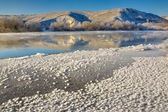 Freezing river from the hilly banks and large ice floes. A sunny day with a cloudless sky Stock Image