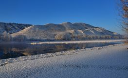 Freezing river from the hilly banks and large ice floes. A sunny day with a cloudless sky Stock Photography