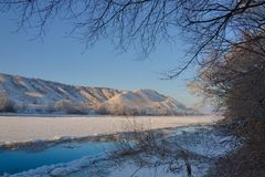 Freezing river from the hilly banks and large ice floes. A sunny day with a cloudless sky Royalty Free Stock Images