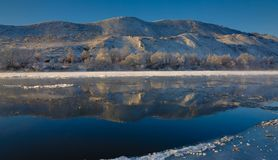 Freezing river from the hilly banks and large ice floes. A sunny day with a cloudless sky Royalty Free Stock Photos