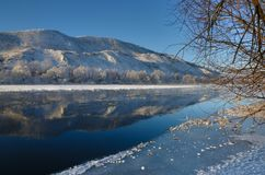 Freezing river from the hilly banks and large ice floes. A sunny day with a cloudless sky Royalty Free Stock Photography