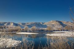 Freezing river from the hilly banks and large ice floes. A sunny day with a cloudless sky Royalty Free Stock Photo