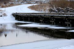Freezing river. Reflection of river bank in freezing water stock photo