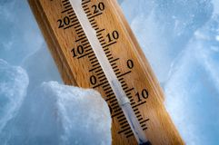 Freezing temperatures and cold weather concept with close up on a vintage thermometer surrounded by blue ice showing sub zero. Temperature stock images