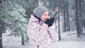 A freezing tourist woman drinks hot tea from a mug against the backdrop of a winter forest or park on a snowy day. Slow stock video footage