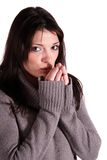 Freezing woman. A womanblows in her hand to warm them up. All isolated on white background Royalty Free Stock Images
