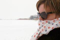 Freezing woman cowers her face with a scarf. She stands next to a frosted lake Royalty Free Stock Image
