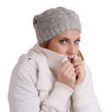 Freezing woman. Young woman wearing woolen hat and winter jacket is freezing Stock Photo