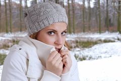 Freezing woman. Young woman wearing woolen hat and winter jacket is freezing Royalty Free Stock Images