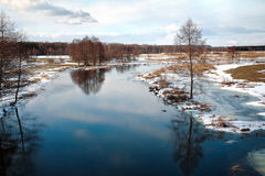 Freezing woody river. Pisa River in the forest. View at the  calm, freezing river surface, at sunny day. Cloudy sky, Masuria, Poland Stock Photo