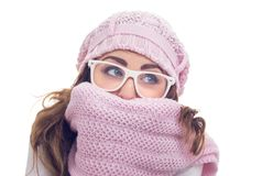 Freezing young woman. Hiding behind her scarf or winter clothing, isolated on white. Close up studio shot Stock Photo
