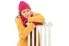 Freezing young woman leaning on a radiator. Isolated on white background stock image