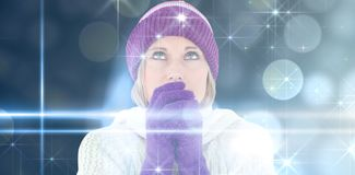 Composite image of freezing young woman wearing gloves looking upwards stock image