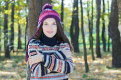 Freezing young woman wearing knitted woolly hat and embracing herself Royalty Free Stock Photo