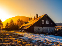 Freezy mountain morning with first beams of rising sun. Mountain hut in first beams of rising sun. Freezy mountain morning in winter time Royalty Free Stock Photo