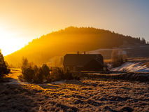 Freezy mountain morning with first beams of rising sun. Mountain hut in first beams of rising sun. Freezy mountain morning in winter time Stock Photo