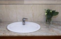 Fregadero con la flor en un cuarto de baño imagenes de archivo