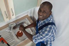 Fregadero de cocina de Using Plunger In del fontanero fotografía de archivo libre de regalías