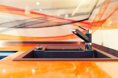 Fregadero de cocina moderno en de cerámica anaranjado foto de archivo