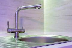 Fregadero del golpecito de agua con el grifo en cocina costosa del desván con la luz de neón fotografía de archivo libre de regalías