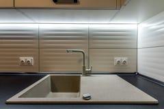 Fregadero del granito y grifo de agua en nuevo interior moderno de la cocina imagen de archivo
