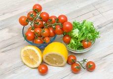 Fregio maturo dei pomodori ciliegia, del limone e dell'insalata Fotografia Stock Libera da Diritti