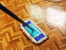 Fregona que lava el piso de madera Foto de archivo