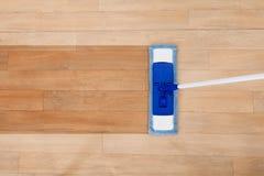 Fregona que limpia un piso de madera imagen de archivo
