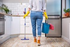 Fregona y cubo de la tenencia de la mujer con los agentes de limpieza en casa fotos de archivo