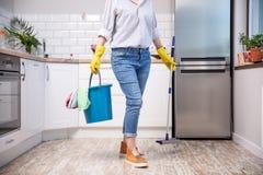 Fregona y cubo de la tenencia de la mujer con los agentes de limpieza en casa fotos de archivo libres de regalías