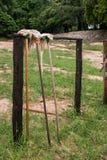 Fregonas viejas que se inclinan contra un soporte de madera Imagen de archivo