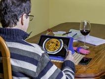 Freiberufler vorbereitet, Lebensmittel von der Tablette auf seinem Schreibtisch zu bestellen Stockfotos