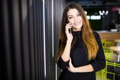 FreiberuflerGeschäftsfrau, die am Handy mit Büroraum im Hintergrund spricht Lizenzfreies Stockbild