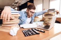 Freiberuflermann, der die Anmerkungen frustriert am Laptop sitzt am Schreibtisch umgeben durch Bücher betrachtet stockbilder