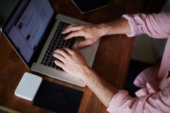 Freiberuflermann, der mit Digitalrechner auf schöner Website arbeitet Lizenzfreie Stockfotos