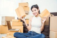 Freiberuflich tätige Frau, welche die Kästen zu Hause bearbeiten Konzept hält Lizenzfreies Stockbild