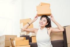 Freiberuflich tätige Frau, welche die Kästen zu Hause bearbeiten Konzept hält Stockfotografie