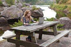 Freiberuflich tätiges Mädchen, das an Laptop in der Natur arbeitet Lizenzfreies Stockbild