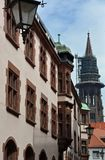 Freiburg Minster view. View through the narrow downtown street lined with historical buildings towards the Cathedral tower during restoration in Freiburg Royalty Free Stock Image