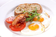 Freid eggs with tomatoes and becon. Stock Photography