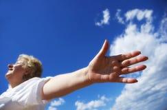 Freie Frau auf dem Himmelhintergrund stockfoto