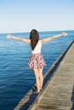 Freie Frau, die den Sommer mit den offenen Armen auf dem Strand genießt Lizenzfreies Stockbild