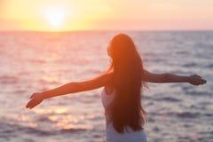 Freie Frau, welche die Freiheit sich fühlt glücklich am Strand bei Sonnenuntergang genießt.