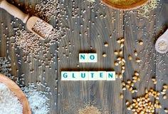 Freie Getreide des Glutens Mais, Reis, Buchweizen, Quinoa, Hirse und Amarant mit Text kein Gluten auf grauem hölzernem Hintergrun stockbilder