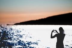 Freie glückliche Frau, die Sonnenuntergang genießt Umfassung das goldene Sonnenscheinglühen des Sonnenuntergangs, Frieden genieße Stockbilder